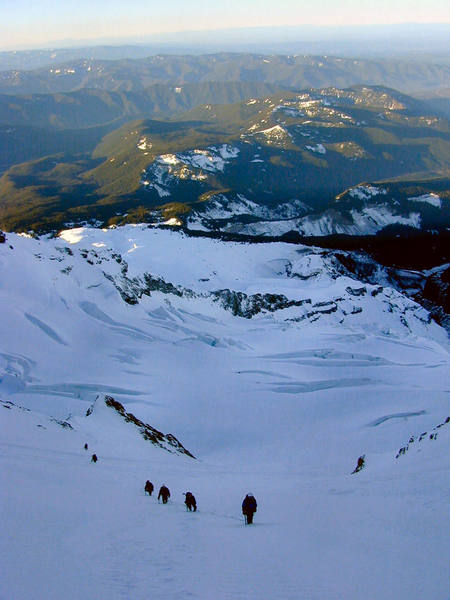 Climbers ascend into Leuthold Couloir with Reid glacier below.