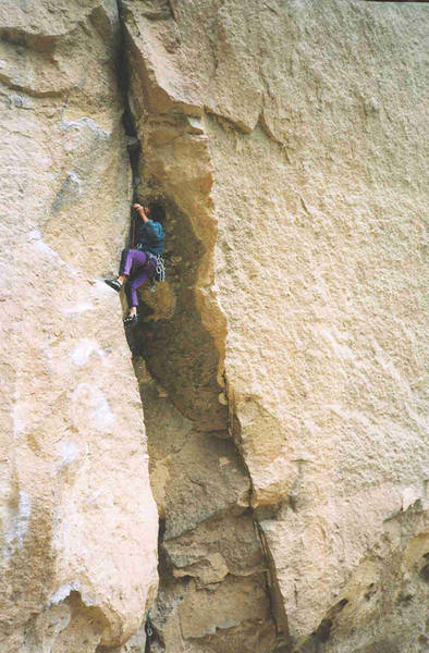 At the hidden crux wondering how secure the holds are in the flare above the bulge. Photo by Gabe C.