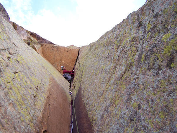 Looking for nonexistent footholds at the start of the 5th pitch.