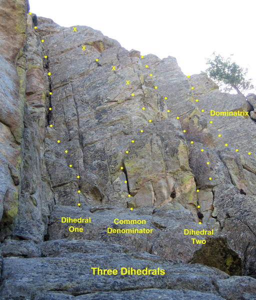 Three Dihedrals.  All climbs start at the base of a low-angle ramp.  <br> <br> Dihedral One takes the steep corner on the left. (5.7)<br> <br> Common Denominator climbs the arete and face right of Dihedral One. (5.9+)<br> <br> Dihedral Two climbs the bushy corner right of Common Denominator. (5.8)<br> <br> Dominatrix is the third dihedral; it starts uphill on the right. (5.8 or 5.10)