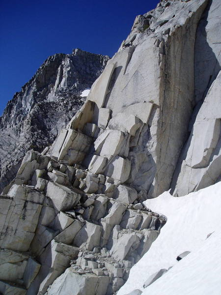 Looking across the gully to the ledges that mark the normal start of the route, which is just below the large detached flake on the left ridge line.