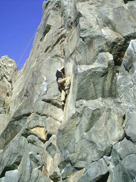 "My brother struggling at the crux of ""Kindling Crack"", one of the classic routes at Long Beach (Dunedin area)."