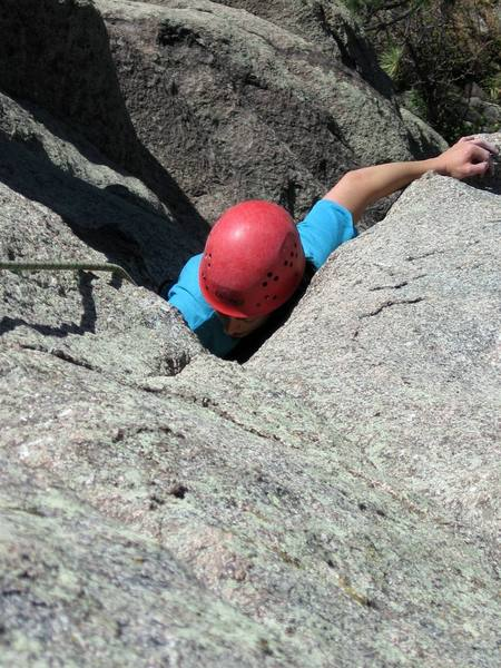 Anna Clarke finishes the great hand jam section with right side in and left out on a bucket on the arete. This is the end of challenging climbing on P1.