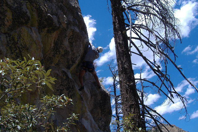 """Pulling through the juggy roof to access the """"great face climbing above."""""""