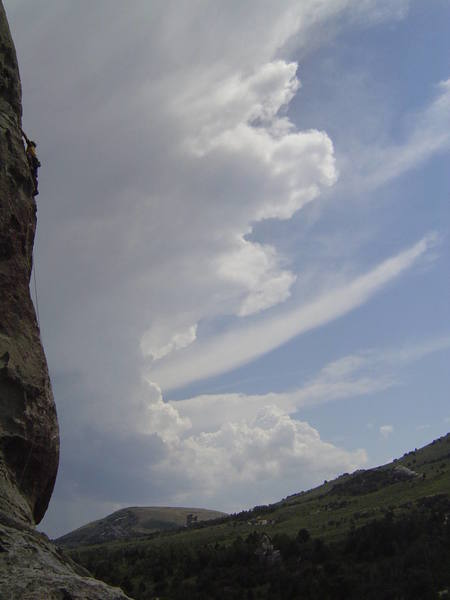 "Matt on the runout section of ""Scream Cheese"" (5.9) with afternoon Thunderheads streaming by"
