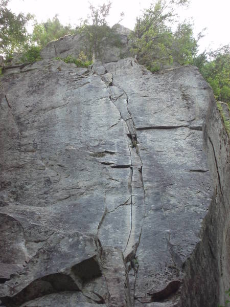 The thin cracks of Even Steven from the ground. The cruxes come at the thin section low on the route (just above the huge ledge) and up higher beyond the slightly broken section.