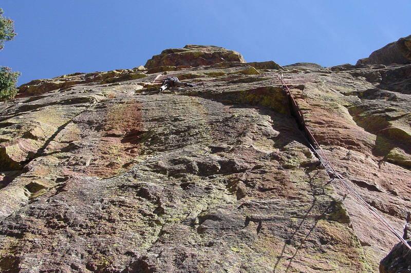 The traverse is easy until this point, when it gets slightly dicey. I'm climbing with double ropes. The left, blue, rope is clipped to the big cam at the top of the wide crack. I climbed several placements from there on the right, red rope, then clipped the blue to the sling over the horn midway across the traverse. I clipped the red after making the first hard move up the left crack. Rope drag was minimal this way, but the ropes are still heavy by the end of this long pitch.<br> <br> Photo by Paul Rezucha.