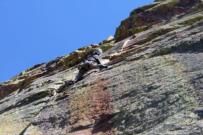 Looking up at the first hard moves in the left crack. The first move to get stood up into the shallow, right-facing corner is easy with a trick, but then it's problematic just staying there due to no handholds.<br> <br> Photo by Paul Rezucha.