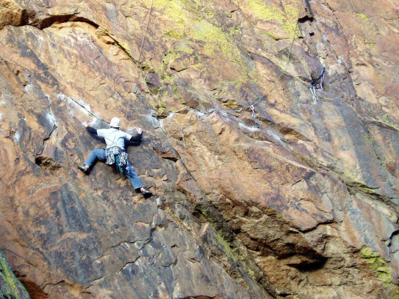 Unknown climber following the downward crux moves beyond the second bolt.