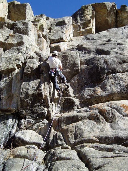Greg has a crummy hold with his left hand. A jug awaits after standing on the arete. Greg ended up skipping the last bolt.