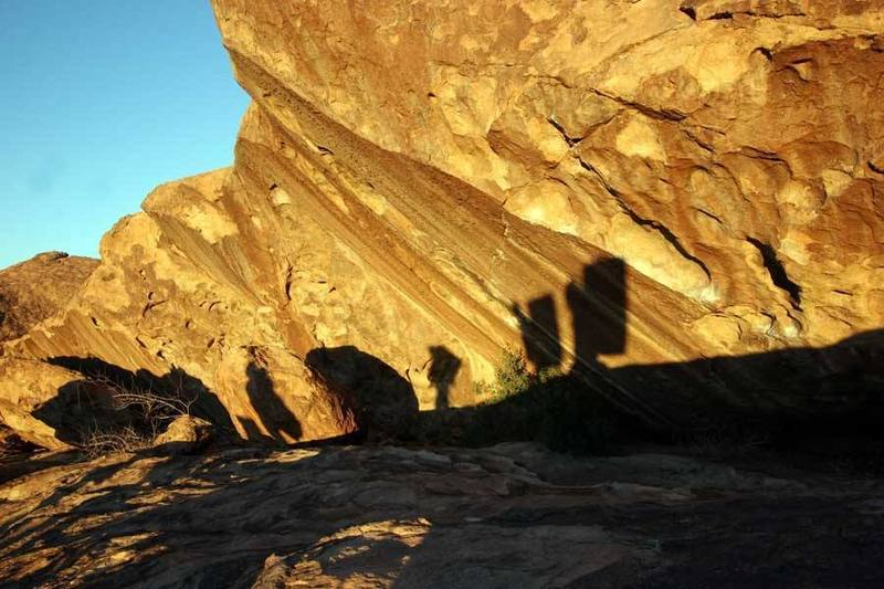 """Boulderers silhouetted on """"Slashface."""""""