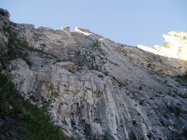 Belaying the 2nd on Apache Line.  The 11d start is to the left.  The rest of the route follows the clean panel of rock to the left of the climber and the gunsight notch on the skyline.