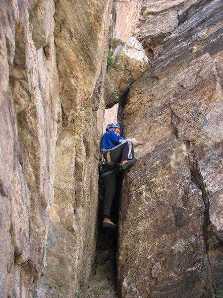 """Bouldering up the short chimney to get to the start of """"Rosie."""""""