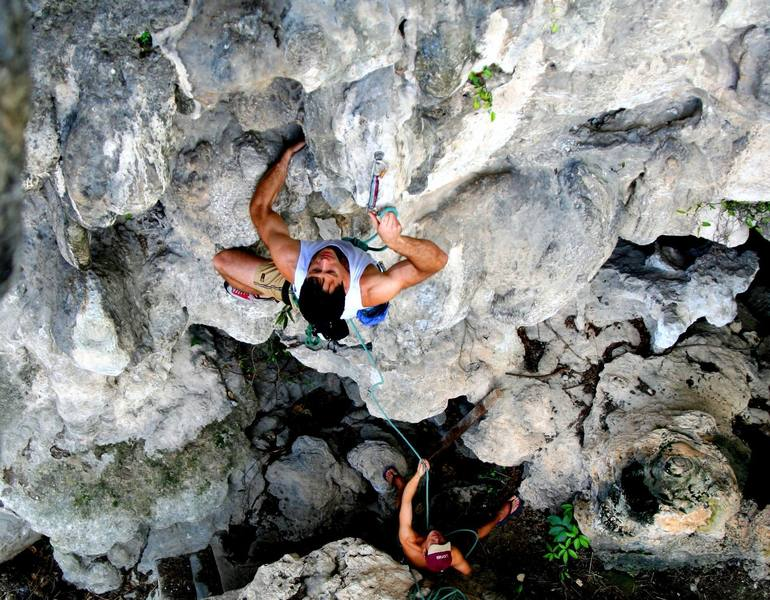 """Tony Bubb enjoying the good """"clipping holds"""" (hardy-har-har) while climbing 'Circumcision (6b)' at Nanyang Wall, in the Batu Caves area of K.L., Malaysia. Photo by Kenny Low, December 2006"""