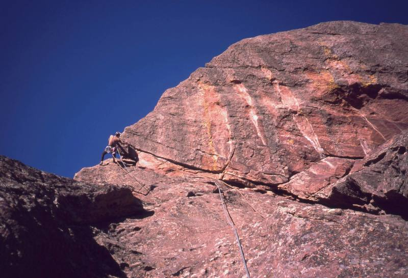 "Tony Bubb negotiates the crux Overhang of the classic ""Satan's Slab (5.8)"" of Skunk Canyon, in the central Flatirons of Boulder. Photo by Peter Spindloe, 2003."
