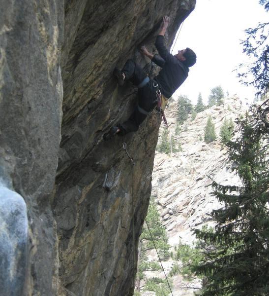 Zach Allen reaching for the crux 2-finger pocket.