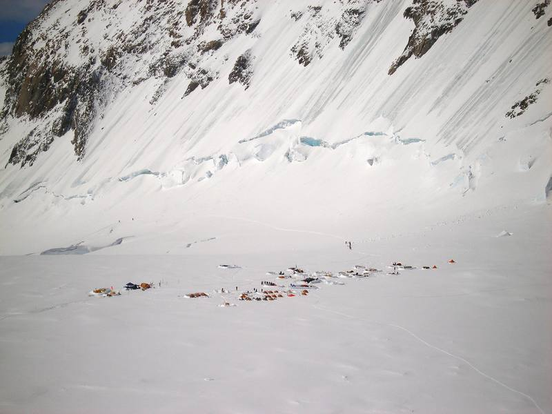 The West Buttress camp at 14,000 feet, viewed from a point below the Orient Express, on the way up the West Rib cutoff.  The tents on the left side of the camp are staffed by the National Park Service, and typically include a rustic medical facility.  The ascent to this camp is via the boot track that is visible beyond the camp.  There are ice climbs on the steep ground above the boot track, on the flank of the West Buttress.  The West Buttress route ascends fixed lines on a slope that is just out of the photo, on the right.