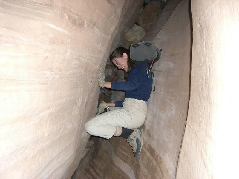 Cheri in the dark slanted slot of White Roost, Utah