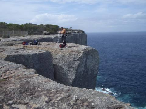 """The Enclosure area above the Lighthouse Area.  Here I am rigging a rap down to the large ledge below """"Northern Exposure"""" et. al.  You can see the fence in the background.  Its not necessary to climb over the fence, just walk around the end of it."""