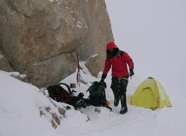 "11. The camp at ~17,200' (?) above the 2nd rock band. After a few days of horrible wind and being shy on food we decided to make a run for the top. When we arrived here, we welcomed the large 'somewhat flat' area, but found it to be sloping ice, which was a lot of work to chop out. Beneath the boulder, you can find an extra rope, full sized spatula (!), and a copy of Tolkien's ""Lord of the Rings""! Not sure why we didn't read it, given the bordem induced by the long storm... Photo by Avery Nelson"