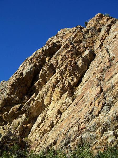 Little Feat starts out in the corner and stays on the sunny face to the right.  Once on the ledge above, follow protection opportunities to the top of the cliff.