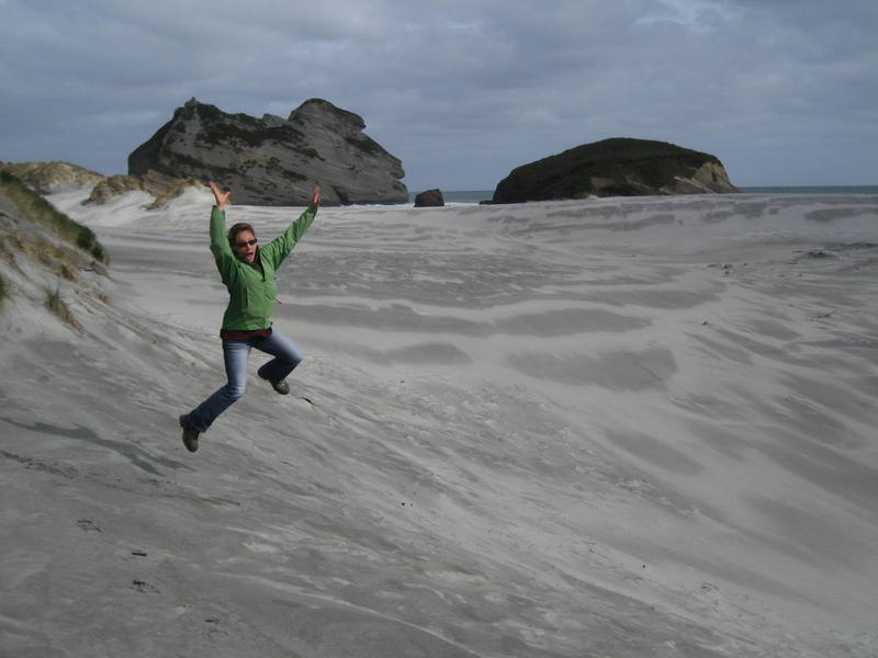Natalie celebrates our arrival on one of the most rugged and desolate beaches we've seen yet in New Zealand, near Farewell Spit on the ocean side of Golden Bay.