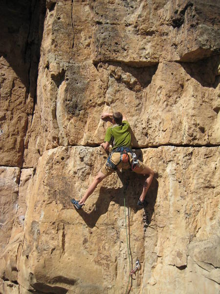Finding some bigger holds above the sketchy rock in the big horizontal crack at about the climber's waist level in this photo.