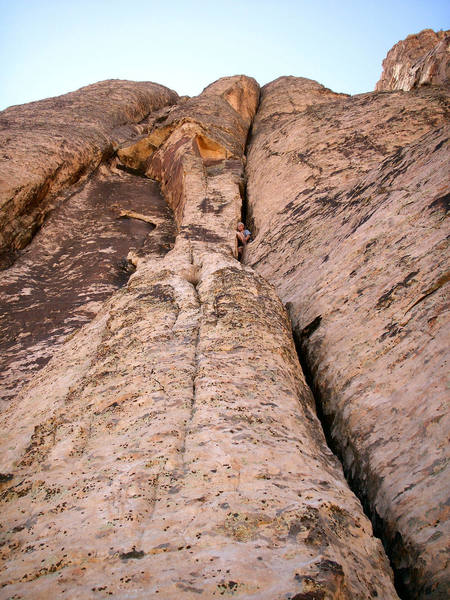 Andrew at pitch 5 belay with wide cracks stretching above.