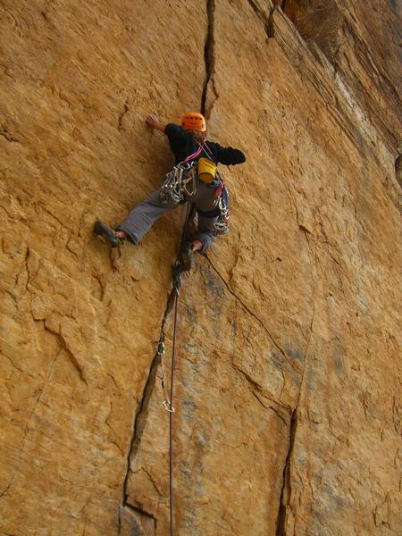 5.9 crack to the right of Community Service.  This route finishes with some 5.10 moves above well placed bolts.  Name?