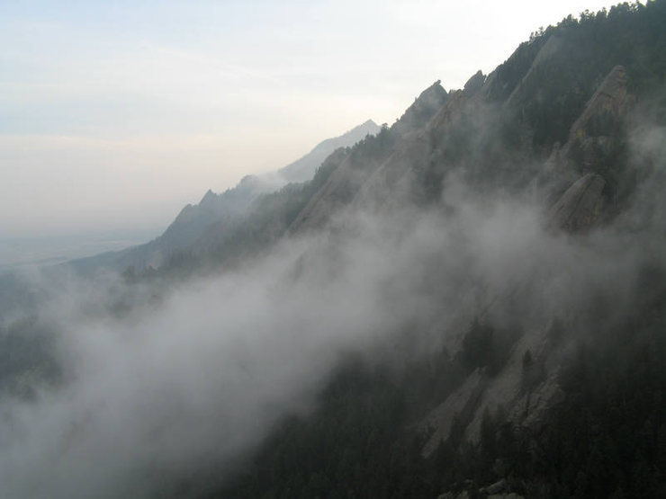 Climbing through the clouds as seen from the Standard East Face on the Third Flatiron.