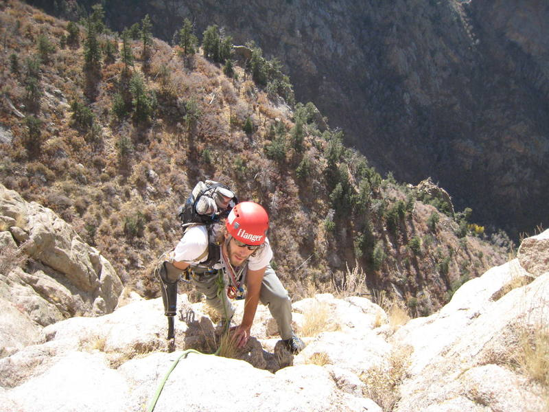 """Aron finishing up P3 into a nice """"belay dish"""" just right of the bushy gully that is frequently belayed from."""