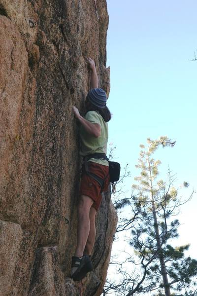 Making the long reach to the shallow break on Sureshot, 5.12a