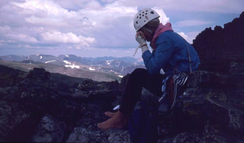 Sarah Shull lets her feet relax on the summit of Sharkstooth after an ascent in 1996.<br> <br> Photo by Tony Bubb.