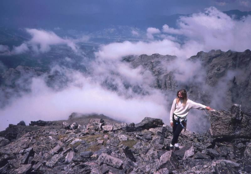 """Sarah Shull hangs out on the summit of Sharkstooth. Although this is the highest summit in the park that lacks a """"non-technical"""" ascent route, it is easily accessible by rock graded at 5.6.<br> <br> Photo by Tony Bubb, 1996."""