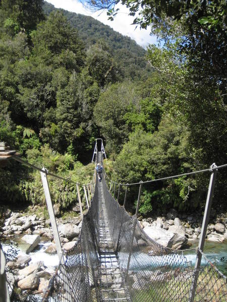 Natalie crossing one of a dozen classic kiwi swing bridges on the Copland Valley trail.