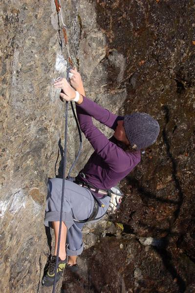 Kayte clipping the bolt after the traverse and before the crux, at the rest jug.