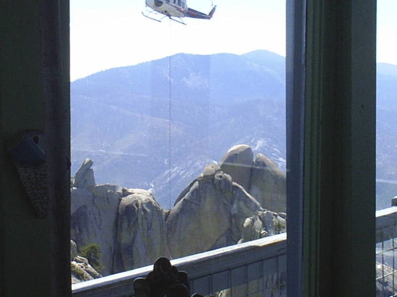 Photo from inside the lookout showing the resupply helicopter.<br> I fly the helicopter and climb Needles on my off time.