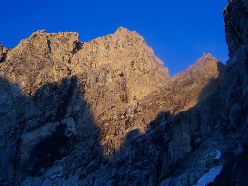 Morning sun on the Grand Teton's north side.  This photo shows the East Ridge, the North Face, the North Ridge, the Grandstand, and Gunsight Notch.  Taken from the Teton Glacier.