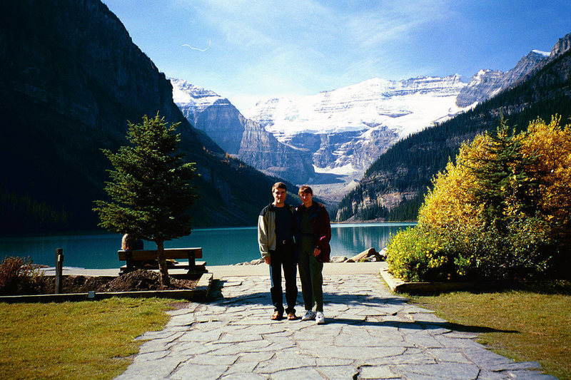 Joanne and I at Lake Louise from the front steps of the Chateau.  Mount Victoria dominates the background and the [[105893648]] crag is visible over Joanne's left shoulder.