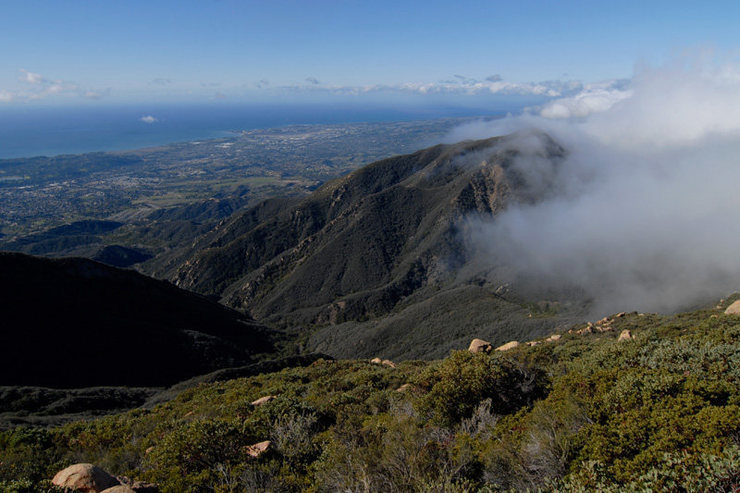 The view west toward UCSB from La Cumbre Peak, as clouds spill over Camno Cielo from the Santa Ynez Valley.