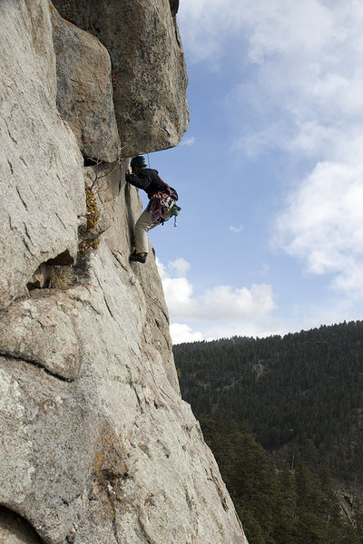 A climber moves out under the roof on the second pitch of Diagonal.