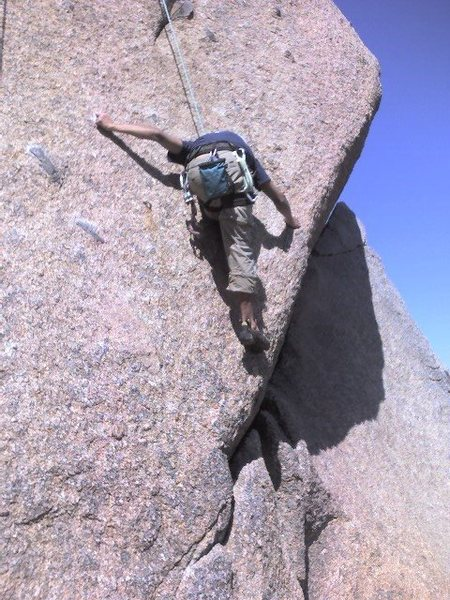 Stepping up on extremely thin holds to get to the lower portion of thin crack that trails downward to right.