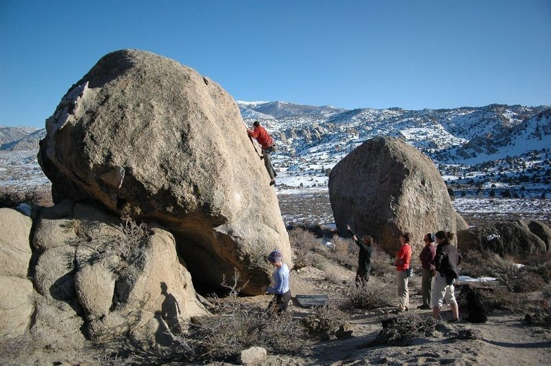 Vicken Hillis on an unnamed v0 on the Buttermilk Stem Boulder.  Rowell Rock is to the right and behind.