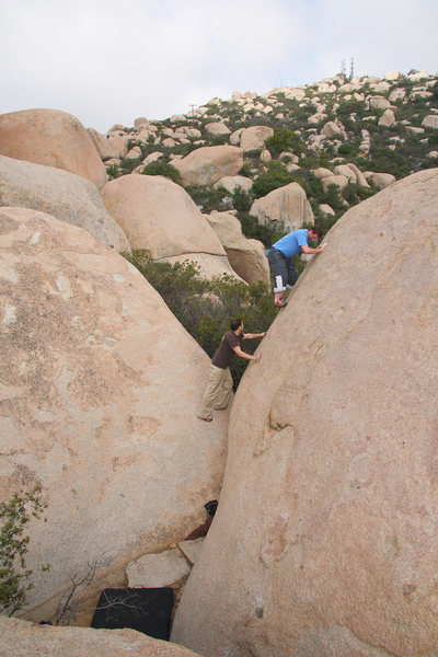 Some people hop off the back.  We thought it was way easier to down-climb(maybe 5.5) the left side onto the boulder that houses   Tricky Face