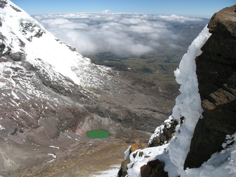 Looking down at the jade green crater lake between the Illinizas as seen from just below the summit of Illiniza Norte. Chimborazo can be seen on the horizon in the distance.