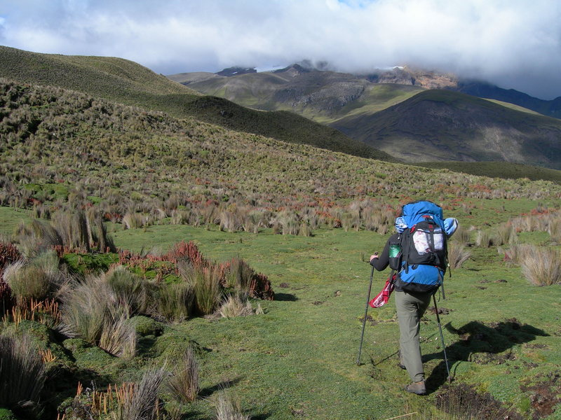 Nancy Bell backpacking near Carihuairazo whose summit is covered in clouds, Ecuador.