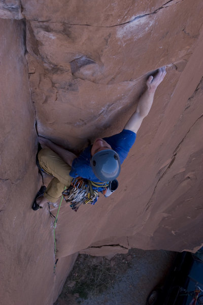 "Adam Perks working through a crux on The Flakes of Wrath (5.9+). This is also where the new variation ""East of Wrath"" moves to the face and continues straight up on horizontal cracks to the new anchor."