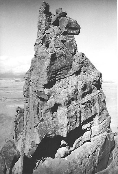 """A view of the main summit from the south summit.  Note the climbers on the horn pitch in the lower-left part of the photograph.  Taken during the """"Ship Rock 30th anniversary ascent"""" in 1969, just before the closure."""