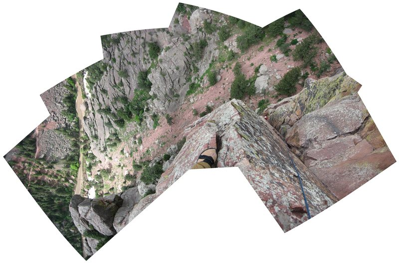 "Looking down from the ""small, exposed belay ledge"" before the crux bolt ladder pitch."