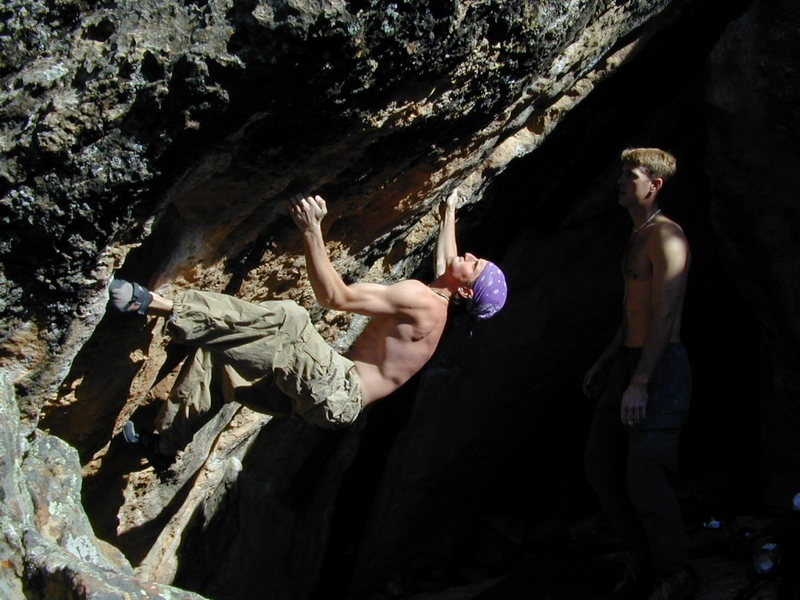 Leif Gasch in mid crux eyes the prize on Two Face V7 in the Bat Cave.